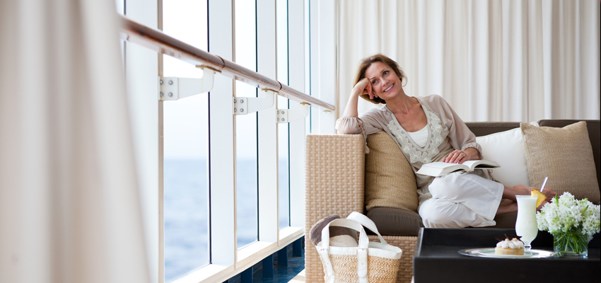 Woman reading book on Regent Seven Seas luxury cruise ship
